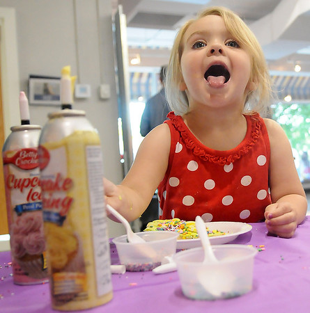 Little Nora Ezzell licks icing off her chin as she decorates a sugar cookie during First Friday activities at the 2nd Story Downtown June 7, 2013. (Staff Photo by BONNIE VCULEK)