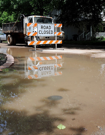 """A """"Road Closed"""" sign reflects in a large area of water as City of Enid Water Reclamation Services' employees repair a broken water main on Pierce, between Cherokee and Oklahoma Thursday, June 6, 2013. Water sprayed into the air and rushed past homes along the neighborhood streets until city employees could shut the valves off to replace the 14 inch line. (Staff Photo by BONNIE VCULEK)"""