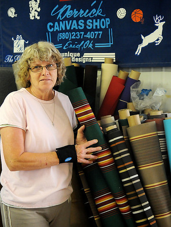 Marilyn Hawkins, owner of Derrick Canvas Shop at 1006 Kline, pauses next to several of her awning fabrics Wednesday, June 12, 2013. (Staff Photo by BONNIE VCULEK)