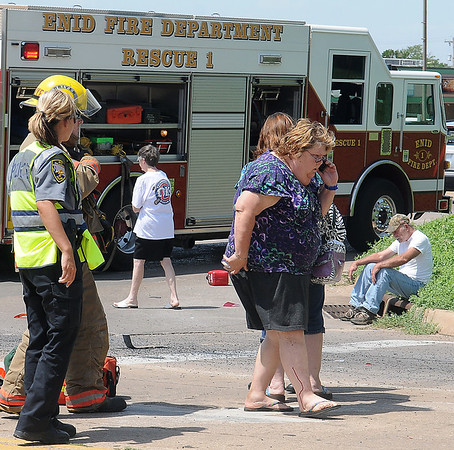 A woman walks to a waiting Life EMS ambulance after Enid firefighters rescued her from her overturned SUV at the intersection of Owen K. Garriott and Johnson Friday, June 22, 2013. (Staff Photo by BONNIE VCULEK)