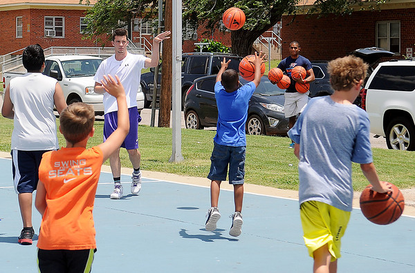 Harrison Maud (back left) tosses a basketball to a waiting youngster as Eduardo Lima carries 4 additional basketballs to the Don Haskins Courts Thursday, June 20, 2013. Maud and Lima, along with Connor Choate, created Give Me A Shot, a 501-C3 that spreads their love of basketball to Enid youth. Donations made to Give Me A Shot were used to purchase 4 new hoops and nets and 25 basketballs for children. (Staff Photo by BONNIE VCULEK)