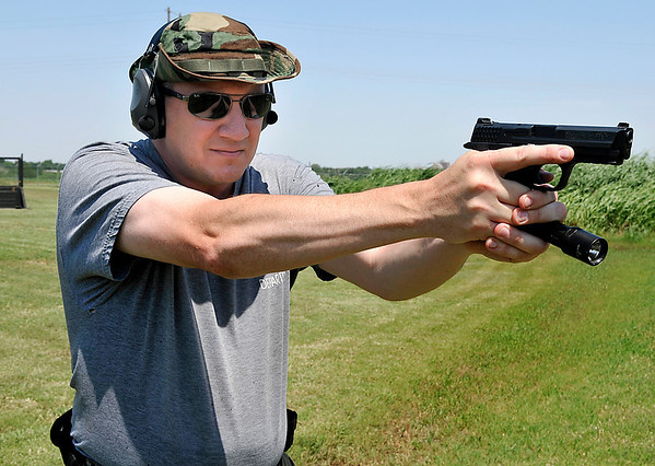 """Lt. Warren Wilson, of the Enid Police Department, demonstrates the """"syringe"""" method of holding a weapon and light. Wilson has an article published in Police Marksman magazine about pros and cons of pistol-mounted lights. (Staff Photo by BILLY HEFTON)"""