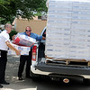 """Capt. Ernie Hull (left) helps Troy Crowley, from O.G.&E. unload 60 - 20"""" Lasko box fans at the Salvation Army Thursday, June 20, 2013. O.G.&E. Corporate office distributes 1,000 fans each year, with a total of 100 donated to Enid, Alva and Woodward this summer. (Staff Photo by BONNIE VCULEK)"""