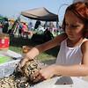 Mia Lavicky creates a pine cone bird feeder during GreEnid at Enid Farmers Market Saturday, June 22, 2013. (Staff Photo by BONNIE VCULEK)