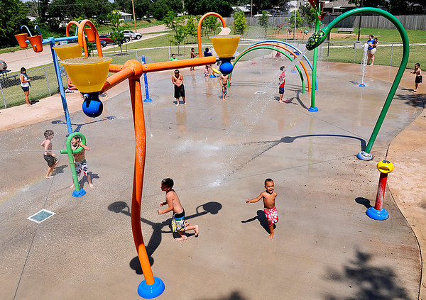 Kids stay cool Tuesday by playing in the water at the Hoover splash pad. (Staff Photo by BILLY HEFTON)