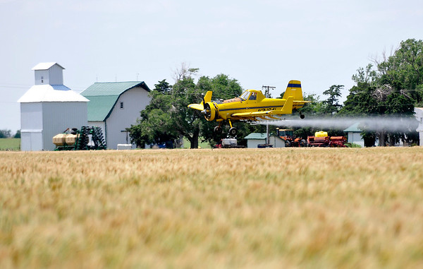 A crop duster makes a pass over a wheat field north of Carrier Tuesday.(Staff Photo by BILLY HEFTON)