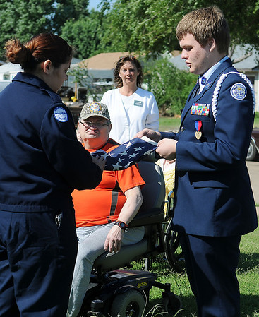 The Living Center residents and staff pause in silence as Enid High School ROTC Cadet Major Laisa Pack (left) and Cadet Sr. MSgt. Zach Willig unfold a new American flag before a special flag raising ceremony at 1409 N. 17th Sunday, June 30, 2013. According to The Living Center Director of Nursing Paula Jessup, Enid Fire Department installed a new rope on the facility's flag pole and Daniel Jessup (back center) provided new hooks so the American flag can now be raised each day by residents, Tom Christianson and Clarence Clark. (Staff Photo by BONNIE VCULEK)