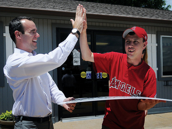 Clint Schelbitzki (left), Union Pacific Director of Public Affairs from Ft. Worth, Tex., receives a high five from Angels' Travis Dunn after Schelbitzki presented 4RKids Foundation with a $15,000 donation toward the renovation of the Miracle League ball field at AMBUCS ABC Park Thursday, June 6, 2013. 4RKids Foundation and Enid AMBUCS have been raising funds for the park improvements for children and adults with special needs. (Staff Photo by BONNIE VCULEK)