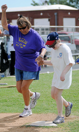 Joan Hampton cheers as she crosses home plate with her granddaughter, Jessica, during the final Miracle League game of the summer at AMBUCS' ABC Park Saturday, June 29, 2013. (Staff Photo by BONNIE VCULEK)