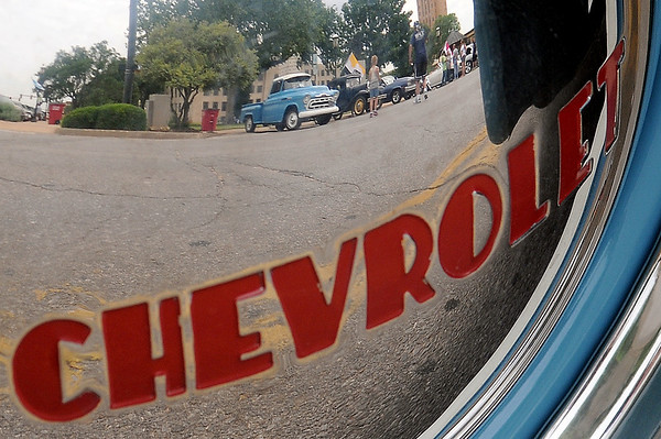 A 1952 Chevrolet pickup hub cap reflects the static display of cars on Randolph during the 3rd annual Van Buren Cruisin Car Show in downtown Enid Saturday, June 15, 2013. (Staff Photo by BONNIE VCULEK)