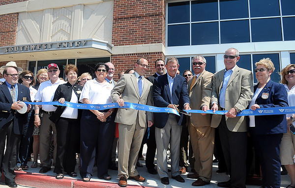 Enid Chamber of Commerce Ambassadors, city commissioners, and other dignitaries watch as Mayor Bill Shewey cuts the ribbon during the grand opening of the new Enid Event Center Wednesday, June 12, 2013. (Staff Photo by BONNIE VCULEK)