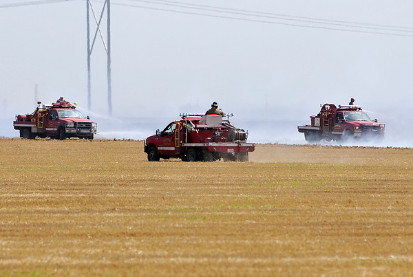 Brush units from numerous fire departments respond to a wheat field fire along Wheat Capital Rd. and between 72nd and 90th streets Monday. (Staff Photo by BILLY HEFTON)
