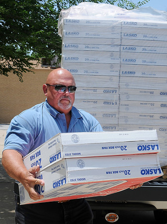 """Troy Crowley, with O.G.&E. delivers 60 - 20"""" Lasko box fans to the Salvation Army Thursday, June 20, 2013. According to Crowley, a total of 110 fans were donated in Enid, Alva and Woodward, with 1,000 distributed across the state from the corporate office of O.G.&E. (Staff Photo by BONNIE VCULEK)"""
