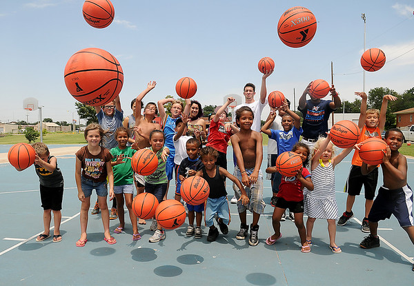 Children toss their new basketballs, from Give Me A Shot's Harrison Maud (back row, third from right) and Eduardo Lima (back, far right), as the youth practice basic skills during a mini-clinic at Don Haskins Court Thursday, June 20, 2013. Give Me A Shot, a 501-C3 organization created by Maud, Lima and Connor Choate, used donations to purchase new hoops and 25 basketballs for children. (Staff Photo by BONNIE VCULEK)