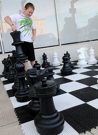Dadrian Whiting moves his queen as he plays a giant chess game with Becky Whiting during First Friday activities in downtown Enid June 7, 2013. (Staff Photo by BONNIE VCULEK)