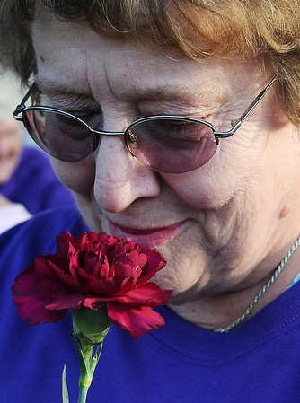 Marilyn Haws, a six-year cancer survivor, smells a beautiful carnation that was given to her by the Relay for Life committee members before the survivors' victory lap in downtown Enid Friday, June 7, 2013. (Staff Photo by BONNIE VCULEK)