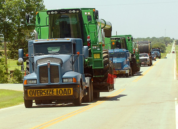 Tractor trailers haul combines along Highway 51 west of Hennessey Monday. The wheat harvest is expected to begin Wednesday. (Staff Photo by BILLY HEFTON)