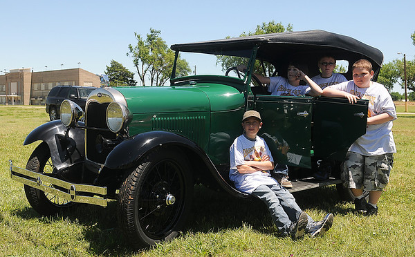 Cimarron Chapter members (from left) Dylan Neuerburg, Walker Pritchett, Dawson Heffron and Joshua Semrad relax on a 1929 Ford Model A during the Boy Scouts of Ameica Car Show at the Garfield County Fair Grounds Saturday, June 1, 2013. (Staff Photo by BONNIE VCULEK)