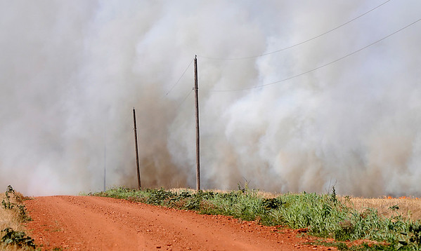 Smoke from a wheat field fire obscures 78th street Monday. (Staff Photo by BILLY HEFTON)
