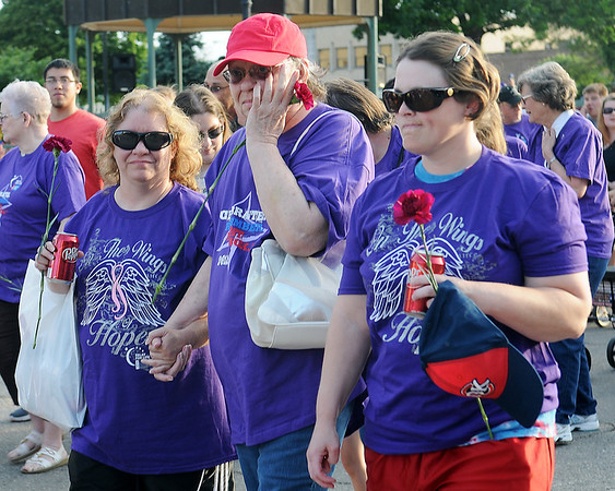 A cancer survivor (center) wipes away a tear as she walks with other survivors and caregivers during the Relay for Life survivors' victory lap around Enid's downtown square Friday, June 7, 2013. Hundreds of purple and yellow balloons filled the sky as the walk began. (Staff Photo by BONNIE VCULEK)