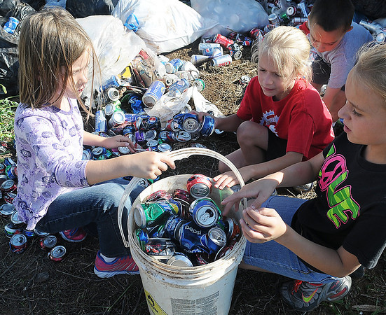 Jordan Bailey, Taryn and Taylor Ellis place aluminum cans into a five-gallon bucket during the Wildhorse Gang can round-up in Kremlin Tuesday, June 11, 2013. (Staff Photo by BONNIE VCULEK)