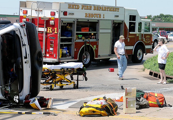 A man and a woman wait at the intersection of Owen K. Garriott and Johnson after the vehicle they were in was involved in a crash with an SUV Friday, June 21, 2013. (Staff Photo by BONNIE VCULEK)