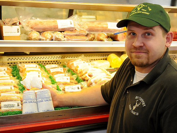 Bob Nafus, with Big Country Meat Market, kneels near the display of summer sausage, beef snack sticks and fresh pork breakfast sausage Wednesday, June 12, 2013. The local business won three 2013 product show awards from the Oklahoma-Texas Meat Processors Association. (Staff Photo by BONNIE VCULEK)