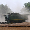 Dust partially obscures the view of a combine as wheat harvest continues around Enid Friday, June 21, 2013. (Staff Photo by BONNIE VCULEK)