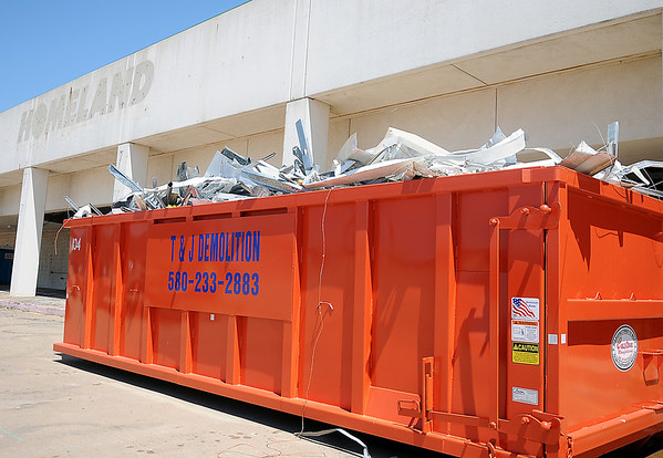 A filled dumpster appears outside the old Homeland location on W. Owen K. Garriott as crews with Dobler, L.L.C. from Kansas, begin the demolition inside the facility Tuesday, June 18, 2013. (Staff Photo by BONNIE VCULEK)