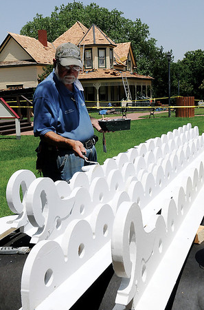 Mike Caffey, Maintenance Director for the Cherokee Strip Regional Heritage Center, puts the finishing touches on new handmade trim for the roof of the 1905 Glidewell House, built by James W. and Alice Glidewell, at Humphrey Heritage Village Wednesday, June 26, 2013. (Staff Photo by BONNIE VCULEK)
