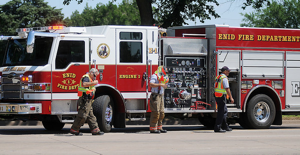 Enid firefighters put on their vests as they assist at an hydraulic fluid spill at the corner of N. Grand and E. Willow Tuesday, June 18, 2013. (Staff Photo by BONNIE VCULEK)