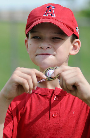 Connor Ganz smiles as he holds his Miracle League medallion Saturday, June 29, 2013. (Staff Photo by BONNIE VCULEK)