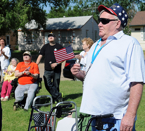 Tom Christianson (right) waves a small American flag as residents and staff applaud during the raising of a new American flag by Enid High School ROTC cadets at The Living Center, 1409 N. 17th, Sunday, June 30, 2013. Christianson and Clarence Clark (seated, front left) will assume the duties of raising the flag each day. (Staff Photo by BONNIE VCULEK)