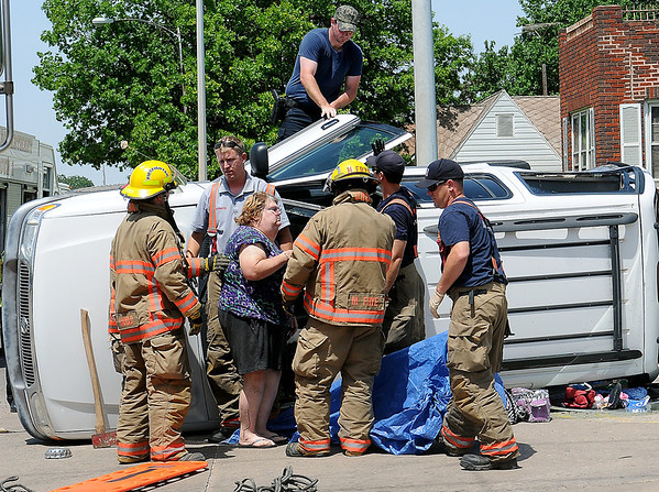 Enid firefighters rescue a woman from and overturned SUV after a crash at Owen K. Garriott and Johnson Friday, June 21, 2013. Enid Fire Department, Enid Police Department and Life EMS responded to the scene. (Staff Photo by BONNIE VCULEK)