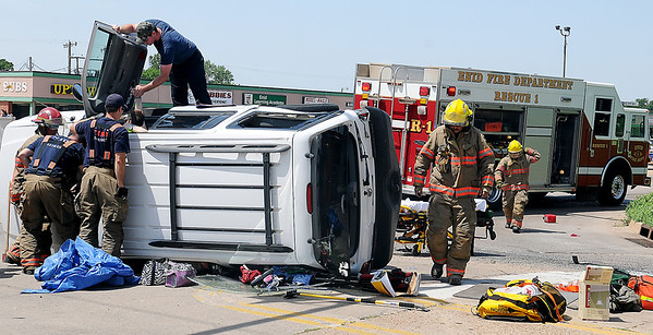 A gentleman (top) holds the hand of a crash victim as Enid firefighters work to free her from her overturned SUV at the corner of Owen K. Garriott and Johnson Friday, June 21, 2013. (Staff Photo by BONNIE VCULEK)