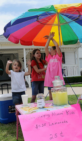 Lakyn Starr Young (left), 4, cheers with her friends, Madelyn Sutton and Taylor Wieden, as Young raises money at her lemonade stand to buy toys for the children in Moore who were affected by the May 20 tornado. As of 1:30 p.m. Saturday, she had collected nearly $500. (Staff Photo by BONNIE VCULEK)