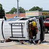An Enid firefighter climbs out of an overturned SUV after firefighters rescued a woman from the vehicle Friday, June 21, 2013. (Staff Photo by BONNIE VCULEK)