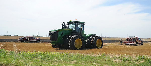 As Enid firefighters get a wheat field blaze under control, an area farmer uses his John Deere tractor to pull two Enid Fire Department grass rigs out of the muddy field. (Staff Photo by BONNIE VCULEK)
