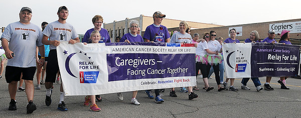 Cancer survivors and their caregivers react to cheers as they take their survivor's victory lap during Relay for Life in downtown Enid Friday, June 7, 2013. (Staff Photo by BONNIE VCULEK)