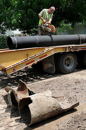 A City of Enid Water Reclamation Services employee cuts a new 14 inch pipe section to replace the broken water main along Pierce Street, between Cherokee and Oklahoma Thursday, June 6, 2013. (Staff Photo by BONNIE VCULEK)