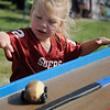 Emma Carter watches her potato car sprint down the track during GreEnid at Enid Farmers Market Saturday, June 22, 2013. Parents and their children created their own car designs and then took turns racing them during the event. (Staff Photo by BONNIE VCULEK)