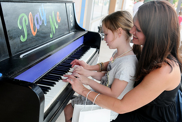 Jelani King and her mom, Lissie, pause along N. Independence to tickle the keys of an upright piano during First Friday activities in downtown Enid, June 7, 2013. (Staff Photo by BONNIE VCULEK)