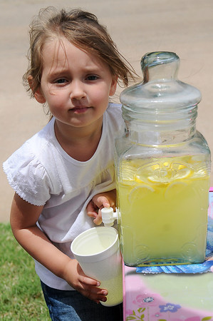 Little Lakyn Starr Young, 4, fills a large cup with lemonade as she raises money for the children who lost their dolls and other toys during the May 20 tornado. Since Friday, Young had raised nearly $500 at her lemonade stand at 2411 W. Maine. (Staff Photo by BONNIE VCULEK)