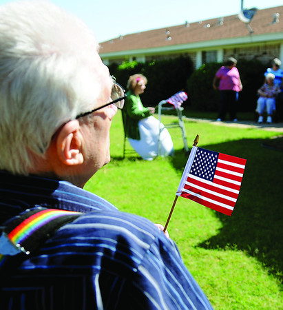 The Living Center residents hold American flags during a special ceremony at 1409 N. 17th Sunday, June 30, 2013. (Staff Photo by BONNIE VCULEK)