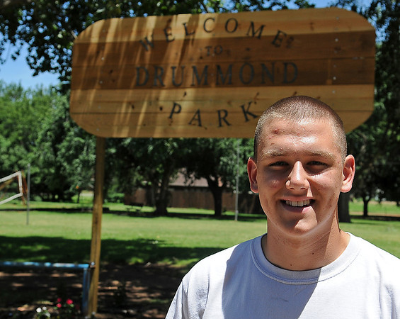 Dillon Throckmorton pauses in front of the new Drummond Park sign that he built for his Eagle Scout rank. The construction began Saturday, June 22 and a few more flowers were added to the entrance gardens Friday, June 28, 2013. Throckmorton, who will depart for his Marine assignment in July,  has volunteered his time to help keep the park clean. (Staff Photo by BONNIE VCULEK)