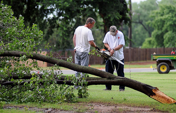 Northern Oklahoma College-Enid maintenance workers repair a chain saw as they remove fallen tree limbs after a severe thunderstorm moved across Garfield County early Wednesday, June 5, 2013. (Staff Photo by BONNIE VCULEK)
