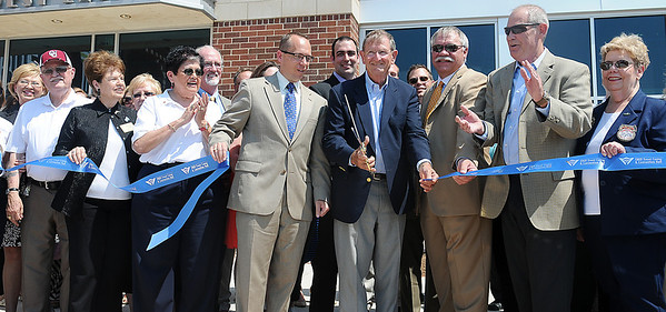 As Enid Mayor Bill Shewey cuts the ribbon, dignitaries celebrate the grand opening of the Enid Event Center Wednesday, June 12, 2013. (Staff Photo by BONNIE VCULEK)
