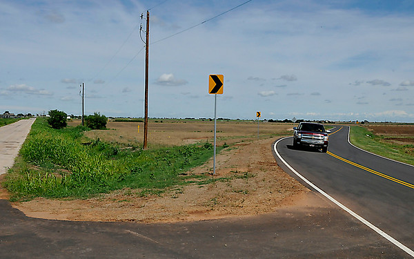 A pick-up travels on the section of Southgate Road that was rerouted for the expansion of a runway at Woodring Airport. (Staff Photo by BILLY HEFTON)