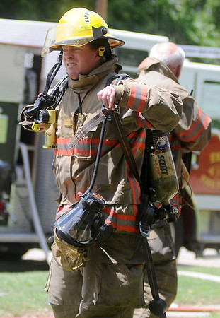 Enid firefighters remove their air packs after battling a structure fire at 324 W. Pine Saturday, June 21, 2014. Enid Fire and Police Departments responded to the scene. (Staff Photo by BONNIE VCULEK)