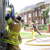 An Enid firefighter takes a drink of water after battling a structure fire as another discharges a 6-inch line at 324 W. Pine Saturday, June 21, 2014. (Staff Photo by BONNIE VCULEK)